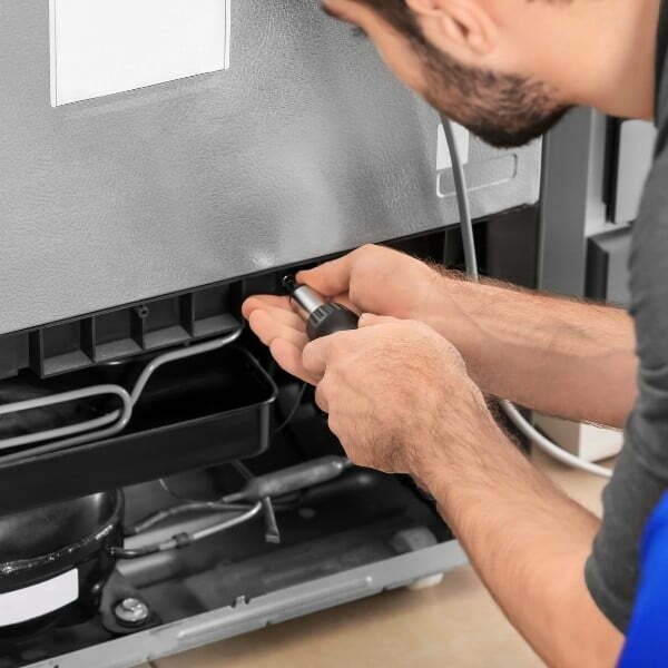 Image depicts a commercial appliance maintenance technician working on a refrigeration unit.
